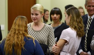 Elizabeth Smart, second from left, speaks with others who attended the committee meeting where a debate on a Utah bill from Salt Lake City Democrat Rep. Angela Romero to teach schoolchildren what to do if they are kidnapped or abused was discussed, Wednesday, Feb. 19, 2014, in Salt Lake City. Smart is backing the proposed measure that would allow public and charter schools to choose if they want to teach the material to children from kindergarten and through high school. (AP Photo/The Salt Lake Tribune, Scott Sommerdorf)
