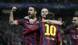 Barcelona's Lionel Messi, center, celebrates scoring the opening goal from a penalty with team mates Cesc Fabregas, left, and Andres Hiniesta during the Champions League first knock out round soccer match between Barcelona and Manchester City at the Etihad Stadium, Manchester, England, Tuesday Feb. 18, 2014. (AP Photo/Jon Super)