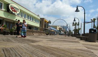 FILE - In this May 22, 2013 file photo, vacationers walk along the boardwalk in Myrtle Beach, S.C. Tourism officials in the resort city worry that the cold winter of 2013-2014 in the North and the Midwest could mean extra school makeup days in those areas that could affect the spring tourism season in South Carolina. (AP Photo/Bruce Smith, file)