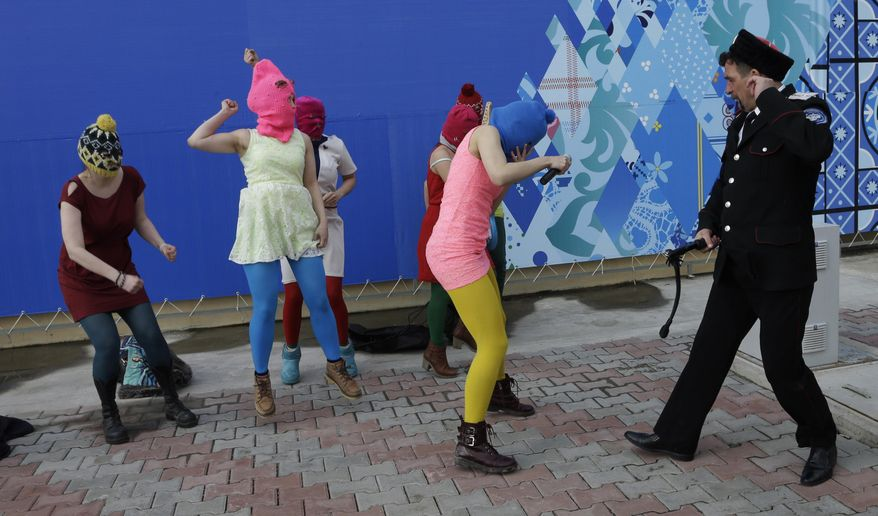Nadezhda Tolokonnikova covers her face as she is attacked by a Cossack militiaman while she and fellow members of the punk group Pussy Riot, including Maria Alekhina, second left, in the pink balaclava, stage a protest performance in Sochi, Russia, on Wednesday, Feb. 19, 2014. The group had gathered in a downtown Sochi restaurant, about 30km (21miles) from where the Winter Olympics are being held. They ran out of the restaurant wearing brightly colored clothes and ski masks and were set upon by about a dozen Cossacks, who are used by police authorities in Russia to patrol the streets. (AP Photo/Morry Gash)