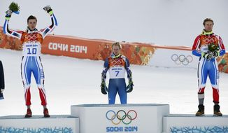 Men's giant slalom medalists, from left, France's Steve Missillier (silver), United States' Ted Ligety (gold) and France's Alexis Pinturault (bronze) take part in a flower ceremony at at the Sochi 2014 Winter Olympics, Wednesday, Feb. 19, 2014, in Krasnaya Polyana, Russia.(AP Photo/Christophe Ena)