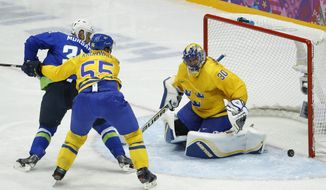 Sweden goaltender Henrik Lundqvist blocks a shot by Slovenia forward Jan Mursak as Sweden defenseman Niklas Kronwall helps defend in the second period of a men's ice hockey game at the 2014 Winter Olympics, Wednesday, Feb. 19, 2014, in Sochi, Russia. Sweden won 5-0. (AP Photo/Mark Humphrey)