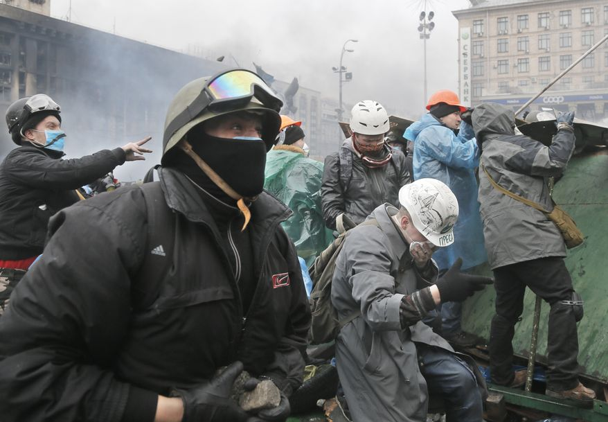 Anti-government protesters throw stones during clashes with riot police in Kiev's Independence Square, the epicenter of the country's current unrest, Kiev, Ukraine, Wednesday, Feb. 19, 2014. The deadly clashes in Ukraine's capital have drawn sharp reactions from Washington, generated talk of possible European Union sanctions and led to a Kremlin statement blaming Europe and the West. A roundup of some of the international reactions. (AP Photo/Efrem Lukatsky)