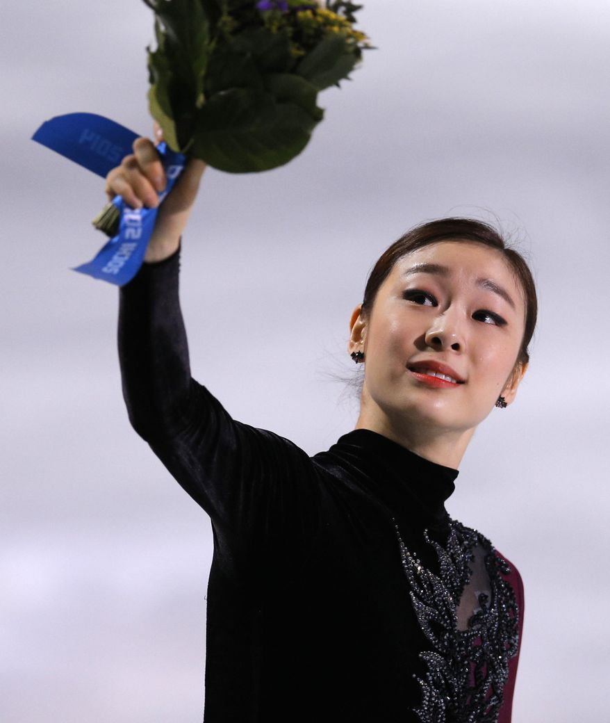 Yuna Kim of South Korea celebrates her second place as she stands on the podium following the women's free skate figure skating finals at the Iceberg Skating Palace during the 2014 Winter Olympics, Thursday, Feb. 20, 2014, in Sochi, Russia. (AP Photo/Vadim Ghirda)
