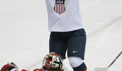 Alex Carpenter of the United States (25) celebrates her goal as Goalkeeper Shannon Szabados of Canada (1) lies on the ice during the third period of the women's gold medal ice hockey game at the 2014 Winter Olympics, Thursday, Feb. 20, 2014, in Sochi, Russia. (AP Photo/Julio Cortez)