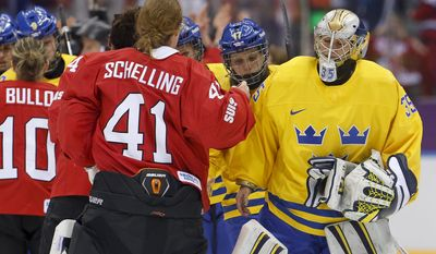 Goalkeeper Valentina Wallner of Sweden (35) congratulates goalkeeper Florence Schelling of Switzerland (41) after Switzerland beat Sweden 4-3 in the women's bronze medal ice hockey game at the 2014 Winter Olympics, Thursday, Feb. 20, 2014, in Sochi, Russia. (AP Photo/Mark Humphrey)
