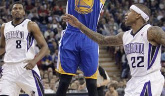 Golden State Warriors guard Stephen Curry goes up for a shot between  Sacramento Kings' Rudy Gay, left, and Isaiah Thomas during the first quarter of an NBA basketball game in Sacramento, Calif., Wednesday, Feb. 19, 2014. (AP Photo/Rich Pedroncelli0