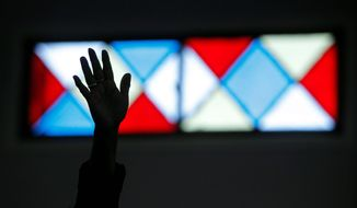 "Hillary Gaxiola raises her hand as she sings during a Sunday service at New Life in Christ Church in Los Angeles. Separated by race for nearly a century, the General Council of the Assemblies of God and the United Pentecostal Council of the Assemblies of God have agreed to a ""cooperating fellowship,"" which includes sharing resources, information and spiritual goodwill. (Associated Press)"