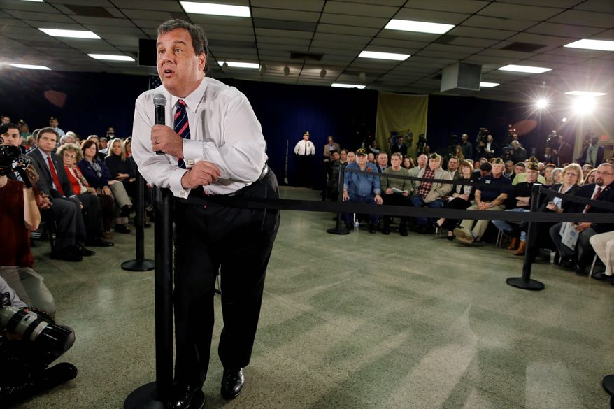 Gov. Chris Christie rests on a post as he addresses a large gathering Thursday, Feb. 20, 2014, in Middletown, N.J., during a town hall meeting. (Associated Press)