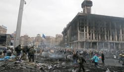 People pass through Independence Square, the epicenter of the country's current unrest, Kiev, Ukraine The flaring of global hot spots such as Ukraine and Syria dramatically illustrates the dwindling influence of President Obama in foreign affairs. (Associated Press)