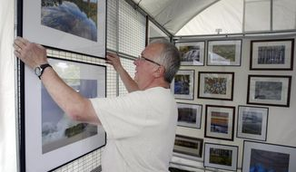 In this July 5, 2013 photo, Paul Peterson hangs his photographs at his booth at Hackley Park for the first Lakeshore Art Festival in downtown Muskegon, Mich.  After an initial year of success and plans for the second year well underway, the new Lakeshore Art Festival has some lofty longer-term goals. The Muskegon Lakeshore Chamber of Commerce,  which last summer rescued the 50-plus years of downtown Muskegon art fairs over the Fourth of July,  has a specific vision of where the two-day event will be in the next three to five years. (AP Photo/The Muskegon Chronicle, Ken Stevens) ALL LOCAL TV OUT; LOCAL TV INTERNET OUT