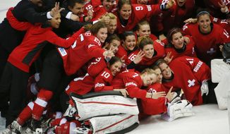 Team Switzerland poses for a picture after their 4-3 win over Sweden in the women's bronze medal ice hockey game at the 2014 Winter Olympics, Thursday, Feb. 20, 2014, in Sochi, Russia. (AP Photo/Julio Cortez)