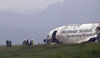 FILE - In this Aug. 14, 2013, file photo, fire crews work the scene of a UPS cargo plane crash at the Birmingham-Shuttlesworth International airport in Birmingham, Ala. Federal investigators are looking at pilot fatigue, among other issues, as a possible factor in the fatal predawn crash of a UPS cargo jet. The National Transportation Safety Board scheduled a hearing for Feb. 20, 2014, on the accident, which killed both pilots.(AP Photo/Butch Dill, File)