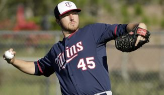 Minnesota Twins pitcher Phil Hughes winds up for a throw during spring training baseball practice Thursday, Feb. 20, 2014, in Fort Myers, Fla. (AP Photo/Steven Senne)