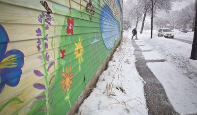 A flowering mural stood in great contrast to the snowy weather outside Phil Anderson's business (Atlantic Press Inc.) as he shoveled the sidewalk during what weather experts were predicting was the largest snowfall of the year thus far on Thursday, Feb. 20, 2014 in Minneapolis, Minn. (AP Photo/The Star Tribune, Renee Jones Schneider)