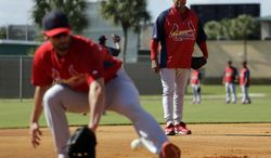 Former St. Louis Cardinals shortstop and Major League Baseball Hall of Famer Ozzie Smith, right, watches as Matt Carpenter works out at third base during spring training baseball practice Tuesday, Feb. 18, 2014, in Jupiter, Fla. (AP Photo/Jeff Roberson)