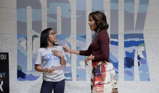 First lady Michelle Obama talks with Sophia Rose Stewart-Chapman, of New York's Little Red School House, in front of a color-by-numbers mural featuring the slogan for WAT-AAH!, a line of bottled water targeted to kids and teens, at the New Museum, in New York,  Thursday, Feb. 20, 2014. (AP Photo/Richard Drew)