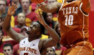 Iowa State forward Melvin Ejim reaches up for the ball after Texas forward Jonathan Holmes blocked his shot during the second half of an NCAA college basketball game at Hilton Coliseum in Ames, Iowa, Tuesday, Feb. 18, 2014. Iowa State won 85-76. (AP Photo/Justin Hayworth)