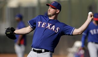 Texas Rangers' Matt Harrison throws in warm ups before a morning workout during spring training baseball practice, Monday, Feb. 17, 2014, in Surprise, Ariz. The Rangers left-hander will have an MRI after back stiffness on Thursday, Feb. 20 kept him from throwing batting practice on the first day of full-squad workouts. (AP Photo/Tony Gutierrez)