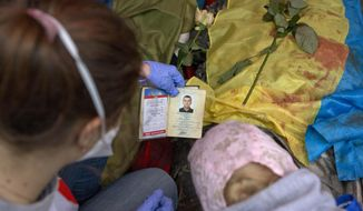 A paramedic looks at the identification document of a killed anti-government protester, in central Kiev, Ukraine, Thursday, Feb. 20, 2014. A brief truce in Ukraine's embattled capital failed Thursday, spiraling into fierce clashes between police and anti-government protesters. (AP Photo/Darko Bandic)