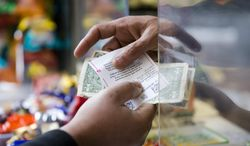 **FILE** Atul Amin, right, sells Powerball tickets at his news stand Wednesday, Feb. 19, 2014, in Philadelphia. The estimated Powerball lottery jackpot is $400 million. (AP Photo/Matt Rourke)