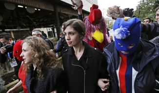 Pussy Riot members Nadezhda Tolokonnikova, center, and Maria Alekhina, left, arrive for a press conference while followed by a person in a chicken costume protesting the punk group - who have feuded with Vladmir Putin's government for years - Thursday, Feb. 20, 2014, in Sochi, Russia. (AP Photo/David Goldman)