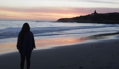 ** FILE ** Shalom Medina, a student at the University of California, Santa Cruz, watches the sunset from the beach at Natural Bridges State Beach on Wednesday, Feb. 19, 2014, in Santa Cruz, Calif. (AP Photo/Marcio Jose Sanchez)