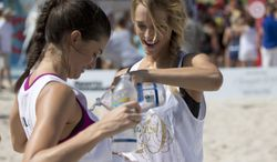 Sports Illustrated swimsuit model Hannah Ferguson, right, pours water over Lauren Mellor after the two finished a volleyball game alongside celebrity chefs in a charity beach volleyball tournament, Thursday, Feb. 20, 2014 on South Beach in Miami Beach, Fla. The chefs, who paid at least $1,000 each for the privilege of playing alongside the models, hit the sand as part of the South Beach Wine and Food Festival. The event raised more than $20,000 for the Armed Forces Foundation and featured models from the 50th anniversary edition of the Sports Illustrated Swimsuit Issue. (AP Photo/Wilfredo Lee)