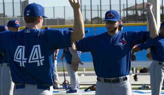 Toronto Blue Jays pitchers Brett Cecil, right, and Casey Janssen (44) warm up at Spring Training in Dunedin, Fla. on Thursday Feb. 20, 2014.  (AP Photo/The Canadian Press, Frank Gunn)