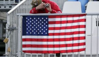 A spectator takes a photo from behind a U.S. flag during men's ski cross competition at the Rosa Khutor Extreme Park, at the 2014 Winter Olympics, Thursday, Feb. 20, 2014, in Krasnaya Polyana, Russia. (AP Photo/Andy Wong)