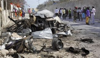 """Somalis gather near the wreckage of one of the vehicles used for a car bomb, following a militant attack on the presidential palace in Mogadishu, Somalia Friday, Feb. 21, 2014. Nine al-Shabab militants wearing military fatigues and carrying guns and grenades died after attacking the presidential palace with two car bombs on Friday, in an assault the president called a """"media spectacular"""" by a """"dying animal."""" President Hassan Sheikh Mohamud was unharmed, but two government officials were killed, the interior ministry said. (AP Photo/Farah Abdi Warsameh)"""