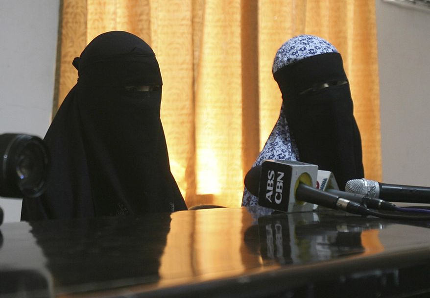 Filipino sisters and independent filmmakers Nadioua Bansil, left, and Linda Bansil, sit following a press conference at the Western Mindanao Command in Zamboanga city, southern Philippines Friday, Feb. 21, 2014. Two Filipino sisters kidnapped by Muslim extremists eight months ago escaped their captors in the jungles of the southern Philippines and told authorities they were kept in isolation in a hut on a meager diet. (AP Photo)