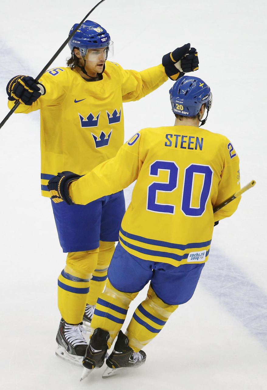Erik Karlsson of Sweden celebrates his goal against Finland with teammate Alexander Steen during the second period of the men's semifinal ice hockey game at the 2014 Winter Olympics, Friday, Feb. 21, 2014, in Sochi, Russia. (AP Photo/Mark Humphrey)