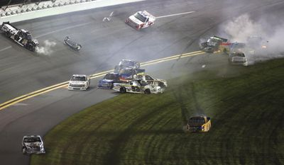 Drivers, including Brian Icker (7), Ross Chastain (92) and Mason Mingus (35), are involved in a crash during the NASCAR Truck Series auto race at Daytona International Speedway in Daytona Beach, Fla., Friday, Feb. 21, 2014. (AP Photo/Jim Topper)
