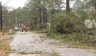 "Crews work in the aftermath of the storm that hit  in the Holly Hill subdivision in northern Laurens County, Ga. on Friday, Feb. 21, 2014. More than 50 homes were impacted by what officials are labeling a ""severe weather event."" (AP Photo/The Courier Herald, Jason Halcombe)"