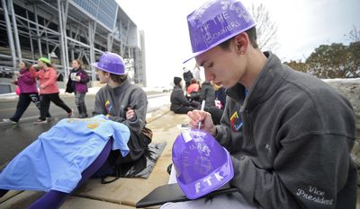 Penn State student Michael Buchanan writes the name of a four diamonds child on a hat he will be wearing as he sits in line for the Penn State IFC/Panhellenic Dance Marathon in University Park, Pa., on Friday, Feb. 21, 2014.   Service organizations started lining up at 5:45 a.m. to get the best seats when the Penn State IFC/Panhellenic Dance Marathon opens its doors at the Bryce Jordan Center.  (AP Photo/Centre Daily Times, Nabil K. Mark)
