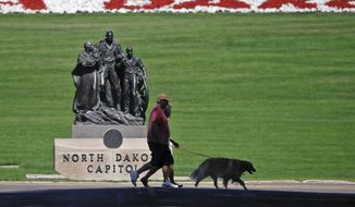 FILE - In this Aug. 19, 2013 file photo, a couple walks a dog in front of the state capitol in Bismarck, N.D. North Dakota leads the nation for well-being according to a survey that takes a look at the physical and emotional health of the nation. The state tops the 2012 Gallup-Healthways Well-Being Index with an overall score of 70.4 out of a possible 100. South Dakota scored an even 70. (AP Photo/The Bismarck Tribune, Tom Stromme, File)