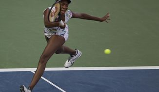 Venus Williams of the U.S. returns the ball to Caroline Wozniacki of Denmark during a semi final match of Dubai Duty Free Tennis Championships in Dubai, United Arab Emirates, Friday, Feb. 21, 2014. (AP Photo/Kamran Jebreili)