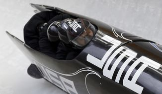 The team from the United States USA-1, piloted by Steven Holcomb, take a curve during the men's four-man bobsled training at the 2014 Winter Olympics, Friday, Feb. 21, 2014, in Krasnaya Polyana, Russia. (AP Photo/Natacha Pisarenko)