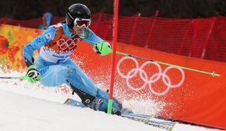 Slovenia's Tina Maze skis past a gate in the first run of the women's slalom at the Sochi 2014 Winter Olympics, Friday, Feb. 21, 2014, in Krasnaya Polyana, Russia. (AP Photo/Luca Bruno)