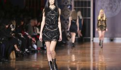 Models wear creations for Versace women's Fall-Winter 2014-15 collection, part of the Milan Fashion Week, unveiled in Milan, Italy, Friday, Feb. 21, 2014. (AP Photo/Antonio Calanni)