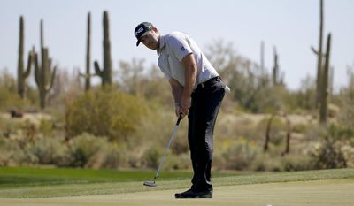 Hunter Mahan putts on the 10th hole in his second-round match against Richard Sterne, of South Africa, at the Match Play Championship golf tournament Thursday, Feb. 20, 2014, in Marana, Ariz. (AP Photo/Matt York)