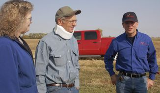 FILE - In this Sept. 27, 2012 file photo, Rose and Dan Dotzenrod, left, talk with Farm Rescue founder and president Bill Gross at the their farm near Wyndmere, N.D. The Dotzenrods were the 200th family to receive assistance from the group that helps farmers who are in need. The North Dakota-based nonprofit that helps farm families plant and harvest their crops is branching out into haying assistance. Farm Rescue is accepting applications from farmers in North Dakota, South Dakota, Minnesota, Iowa and eastern Montana. (AP Photo/Dave Kolpack, File)