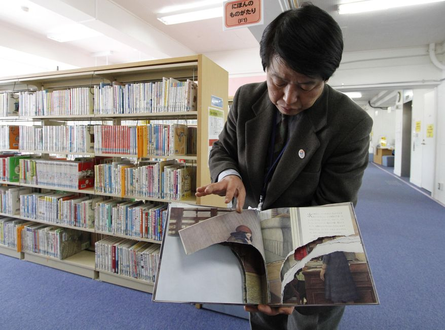 """A ripped copy of Anne Frank's """"Diary of a Young Girl"""" picture book is shown by Shinjuku City Library Director Kotaro Fujimaki at the library in Tokyo Friday, Feb. 21, 2014. (AP Photo/Koji Ueda)"""