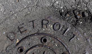 FILE - In an Oct. 10, 2013 photo is a manhole cover is seen in Detroit. The city, which was about to default on a good chunk of a long-term debt exceeding $18 billion, now is getting a second chance in a federal bankruptcy court-led restructuring. (AP Photo/Carlos Osorio, File)