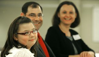 Bria Koch and her parents Brad and Bonnie watch as pictures of Bria flash on a screen during the first annual Bleeding Hearts Luncheon at Billings Clinic on Monday, Feb. 17, 2014. (AP Photo/The Gazette, Larry Mayer)