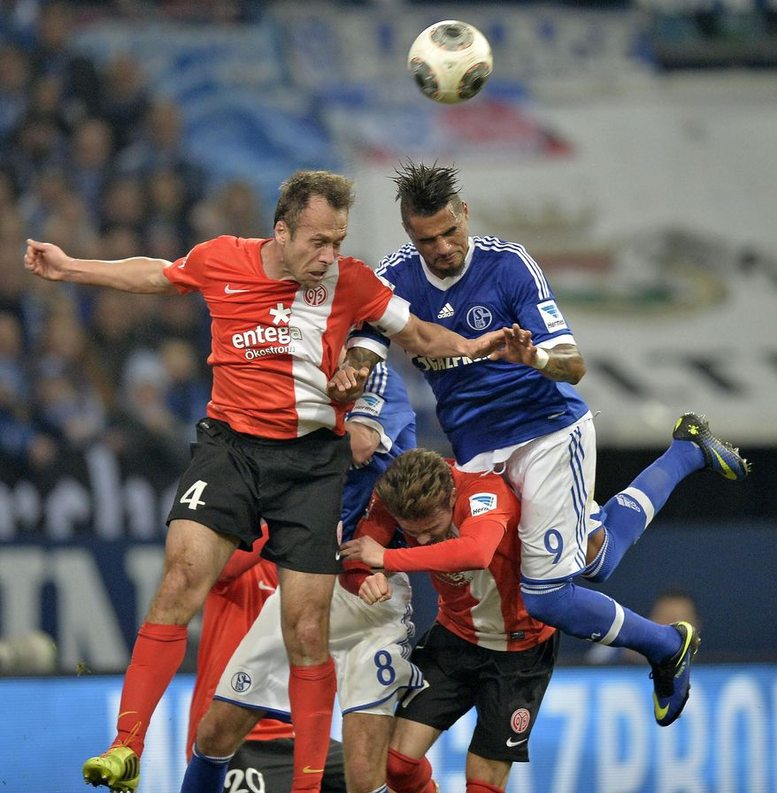 Mainz's Nikolce Noveski, left, and Schalke's Kevin-Prince Boateng, right, challenge for the ball during the German Bundesliga soccer match between FC Schalke 04 and FSV Mainz 05 in Gelsenkirchen,  Germany, Friday, Feb. 21, 2014. (AP Photo/Martin Meissner)