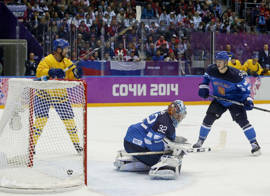 The puck, shot by Sweden defenseman Erik Karlsson, gets past Finland goalkeeper Kari Lehtonen for a goal during the second period of a men's semifinal ice hockey game at the 2014 Winter Olympics, Friday, Feb. 21, 2014, in Sochi, Russia. (AP Photo/Julio Cortez)