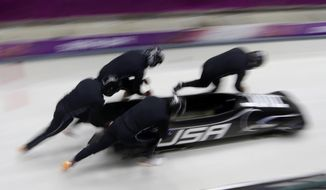 The team from the United States USA-1, piloted by Steven Holcomb, start a run during the men's four-man bobsled training at the 2014 Winter Olympics, Friday, Feb. 21, 2014, in Krasnaya Polyana, Russia. (AP Photo/Dita Alangkara)