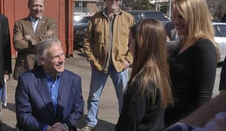 FILE - In this Feb. 18, 2014 file photo Texas gubernatorial candidate Greg Abbott, left, visits with supporters during a stop in Denton, Texas, to promote early voting with Rocker Ted Nugent, wearing cowboy hat, center. Abbott, the leading Republican candidate to succeed Gov. Rick Perry, remained silent about Nugent Friday, Feb. 21, after taking heat this week for inviting the brash gun-rights guitarist to appear with him at campaign events. (AP Photo/The Dallas Morning News, Ron Baselice)